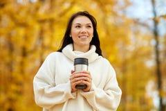 Donna con la bevanda calda in chiavetta al parco di autunno immagine stock