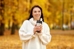 Donna con la bevanda calda in chiavetta al parco di autunno fotografie stock
