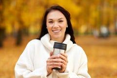 Donna con la bevanda calda in chiavetta al parco di autunno fotografie stock libere da diritti