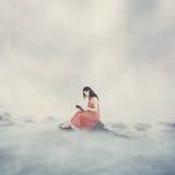 Donna con la bibbia in nuvole. fotografia stock