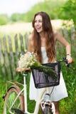 Donna con la bici dalla rete fissa di legno Immagini Stock
