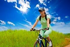Donna con la bici sul campo verde Fotografie Stock Libere da Diritti