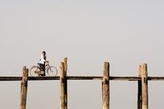 Donna con la bici sul ponte di U Bein in Amarapura, Myanmar (Birmania) Immagini Stock Libere da Diritti