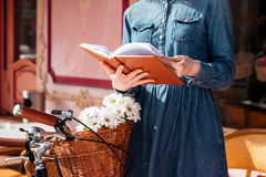 Donna con la bicicletta che legge un libro all'aperto Immagini Stock