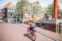 Donna con la bicicletta nella città di Amsterdam fotografia stock libera da diritti