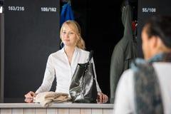 Donna con la borsa che sta al contatore del deposito della borsa fotografie stock libere da diritti