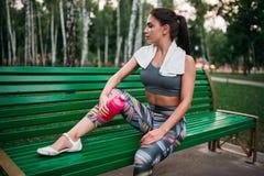 Donna con la bottiglia di sport che si siede su un banco in parco Fotografia Stock
