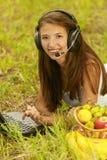 Donna con la bugia della cuffia avricolare su erba Fotografia Stock