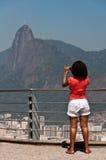 Donna con la camicia rossa che fotografa Cristo il redentore dalla montagna di Sugarloaf Immagini Stock Libere da Diritti