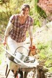 Donna con la carriola che funziona all'aperto nel giardino Fotografia Stock