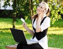 Donna con la carta di credito per mezzo del suo computer portatile. Fotografia Stock