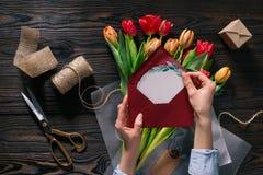 Donna con la cartolina nelle mani ed in tulipani in carta da imballaggio sul ripiano del tavolo di legno Immagine Stock Libera da Diritti