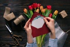 Donna con la cartolina nelle mani ed in tulipani in carta da imballaggio sul ripiano del tavolo di legno Immagini Stock