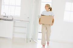Donna con la casella che entra nel nuovo sorridere domestico Fotografia Stock