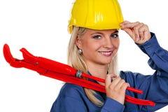Donna con la chiave di tubo e dell'elmetto protettivo Fotografie Stock Libere da Diritti
