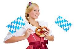 Donna con la ciambellina salata e la bandiera bavarese Fotografie Stock Libere da Diritti