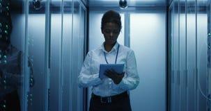 Donna con la compressa che diagnostica l'hardware del server stock footage