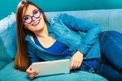 Donna con la compressa che si rilassa sul colore del blu dello strato Immagini Stock Libere da Diritti