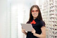 Donna con la compressa del PC in negozio ottico medico Fotografie Stock
