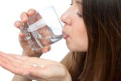 Donna con la compressa della medicina della pillola della presa della mano di emicrania ed il vetro di Fotografia Stock