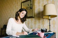 Donna con la compressa digitale che funziona a casa Immagine Stock