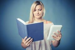 Donna con la compressa tradizionale del lettore del libro elettronico e del libro Immagini Stock Libere da Diritti
