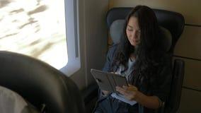 Donna con la compressa in treno video d archivio