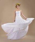 Donna con la corona dei fiori e del vestito d'ondeggiamento Fotografia Stock