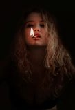 Donna con la corrispondenza illuminata in bocca Fotografia Stock