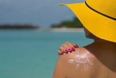 Donna con la crema a forma di Sun del sole sulla spiaggia Fotografia Stock Libera da Diritti