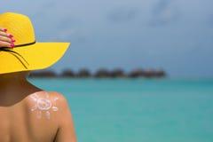 Donna con la crema a forma di Sun del sole sulla spiaggia Immagine Stock