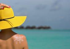 Donna con la crema a forma di Sun del sole sulla spiaggia Immagini Stock Libere da Diritti