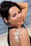 Donna con la crema sole-a forma di del sole Fotografia Stock