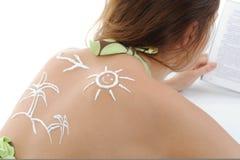 Donna con la crema sole-a forma di del sole Immagini Stock Libere da Diritti
