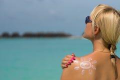Donna con la crema sole-a forma di del sole Fotografie Stock Libere da Diritti