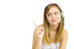Donna con la cuffia avricolare che indica al bianco Fotografia Stock Libera da Diritti