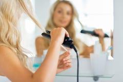 Donna con la designazione del ferro che raddrizza capelli a casa Fotografia Stock Libera da Diritti
