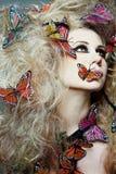 Donna con la farfalla nei capelli ricci. Immagine Stock Libera da Diritti