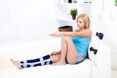 Donna con la ferita di piedino che tiene telecomando fotografie stock libere da diritti