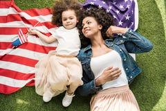 Donna con la figlia sulla bandiera americana Fotografie Stock Libere da Diritti