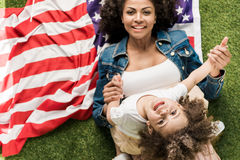 Donna con la figlia sulla bandiera americana Fotografia Stock