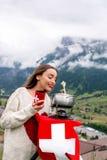 Donna con la fonduta nelle montagne immagine stock