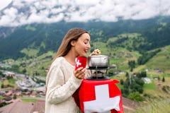 Donna con la fonduta nelle montagne fotografie stock libere da diritti