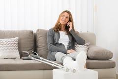 Donna con la gamba intonacata che parla sul telefono cellulare fotografie stock