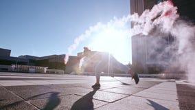 Donna con la granata fumogena che fa frontflip video d archivio
