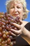 Donna con la grande uva Immagine Stock