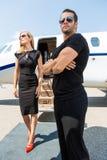 Donna con la guardia del corpo Against Private Jet Immagine Stock