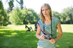 Donna con la macchina fotografica digitale in parco Fotografia Stock