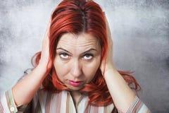 Donna con la mano sulle orecchie fotografia stock libera da diritti