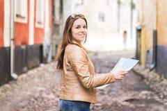 Donna con la mappa che guarda diritto alla macchina fotografica Fotografia Stock